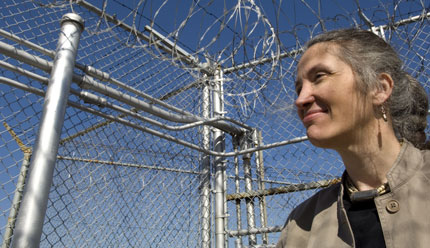 Image of a fence with barbed wire in front of a blue sky with a white woman looking to the left. She is on the right side of the image and is wearing a brown jacket.