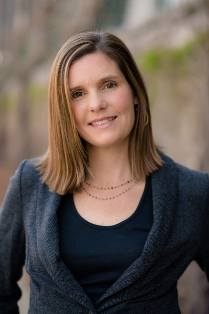Image of white woman with brown hair wearing a black shirt and grey blazer. She is smiling.