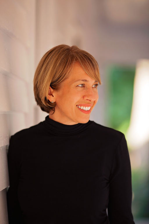Image of a white woman with short blond hair looking to her left and wearing a black shirt.