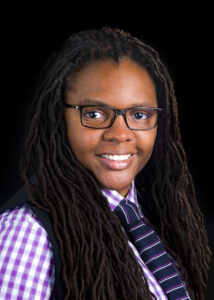 Image of an African American person with long thin dreadlocks, glasses, and a blue and white tie and purple and white button up shirt. They are facing the camera and smiling.