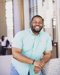 Image of an African American man wearing a short sleeved blue shirt. He is facing the camera and smiling.